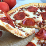 a slice of keto pizza lifted off the plate