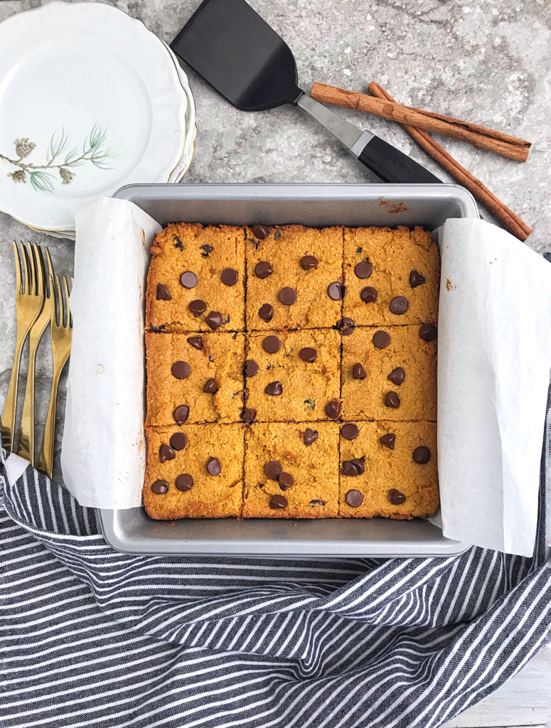 Keto pumpkin chocolate chip blondies sliced up into 9 pieces in a square pan with serving plates and brownie spatular in the background