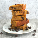 Keto pumpkin Chocolate chip blondies stacked in a plate with chocolate chips tossed around