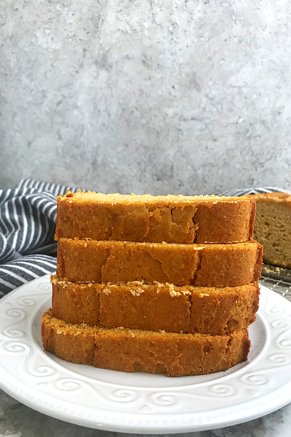 4 keto Pumpkin bread slices stacked on a white plate with a dish cloth in the background