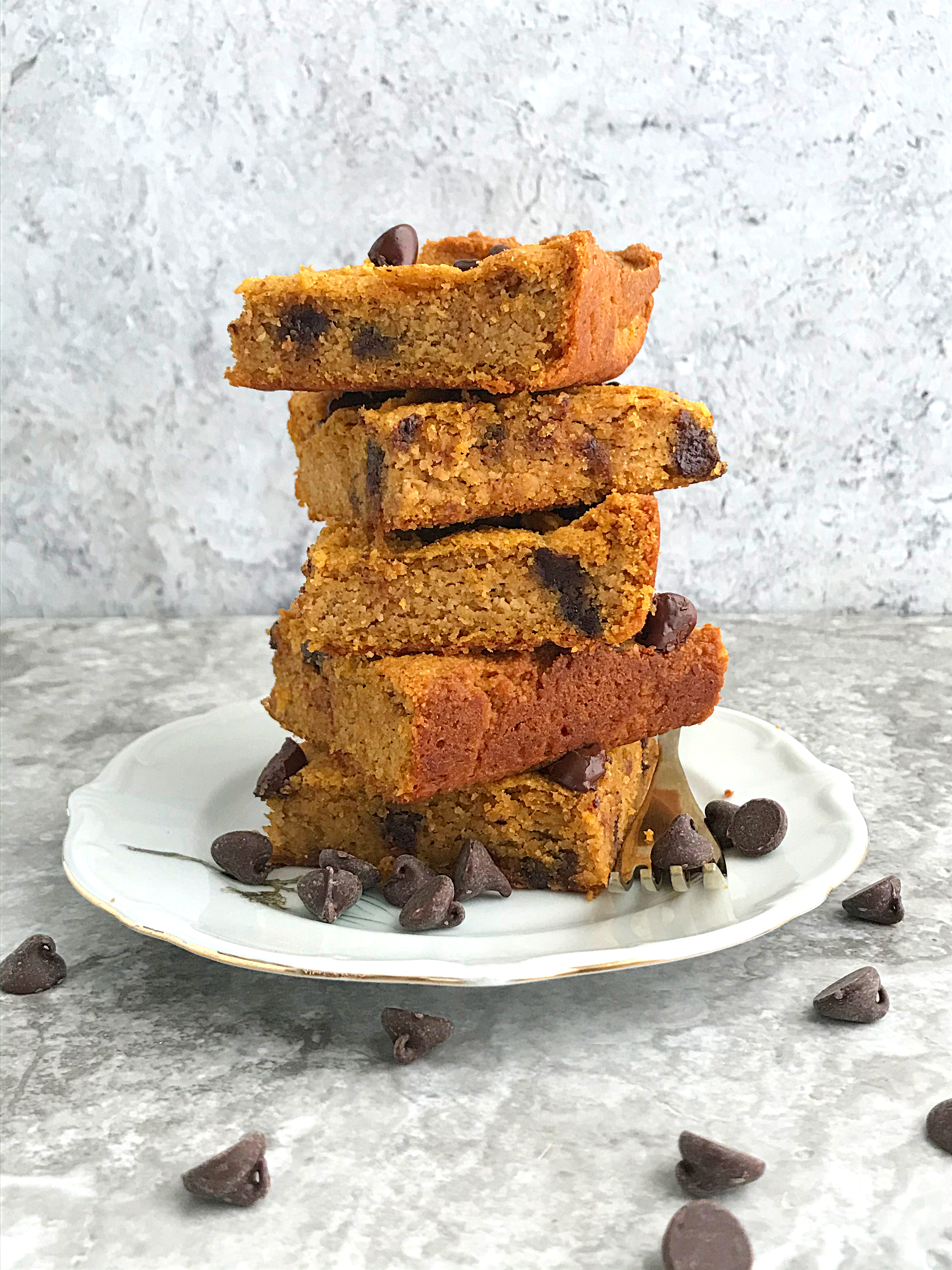 5 Keto Pumpkin chocolate chip blondies stacked in a plate with chocolate chips tossed on the table