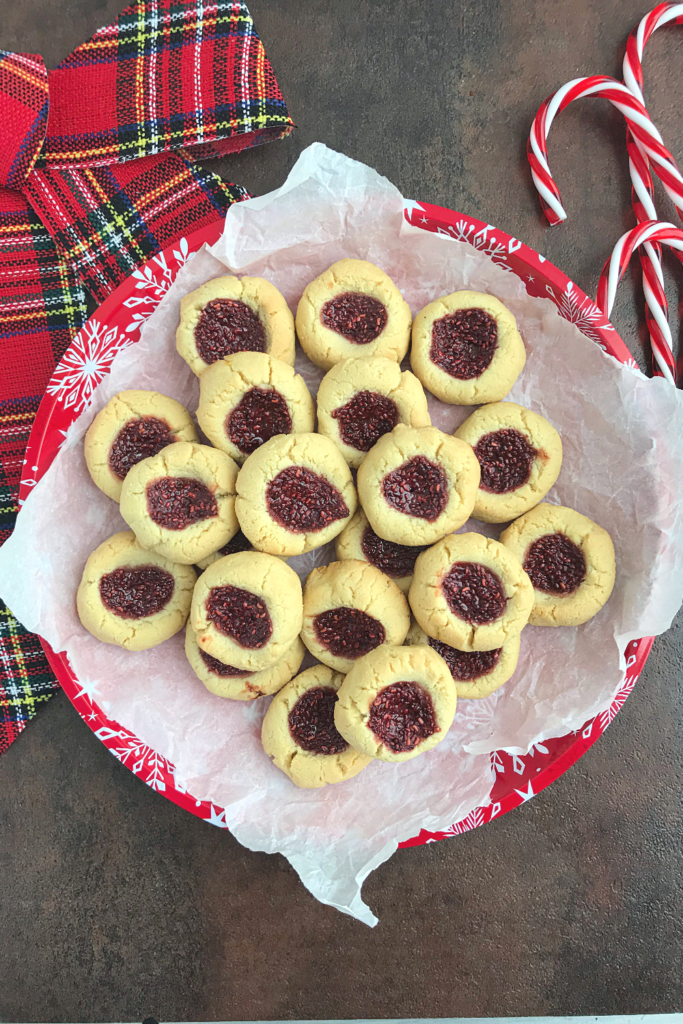 Keto Thumbprint cookies in a red christmas themed plate with candy canes and a lumberjack ribbon at the background