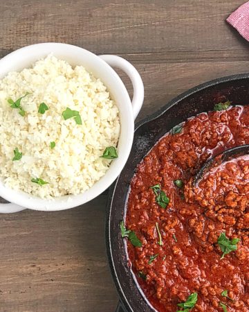 cauliflower rice in a white bowl with a skillet of tomato sauce