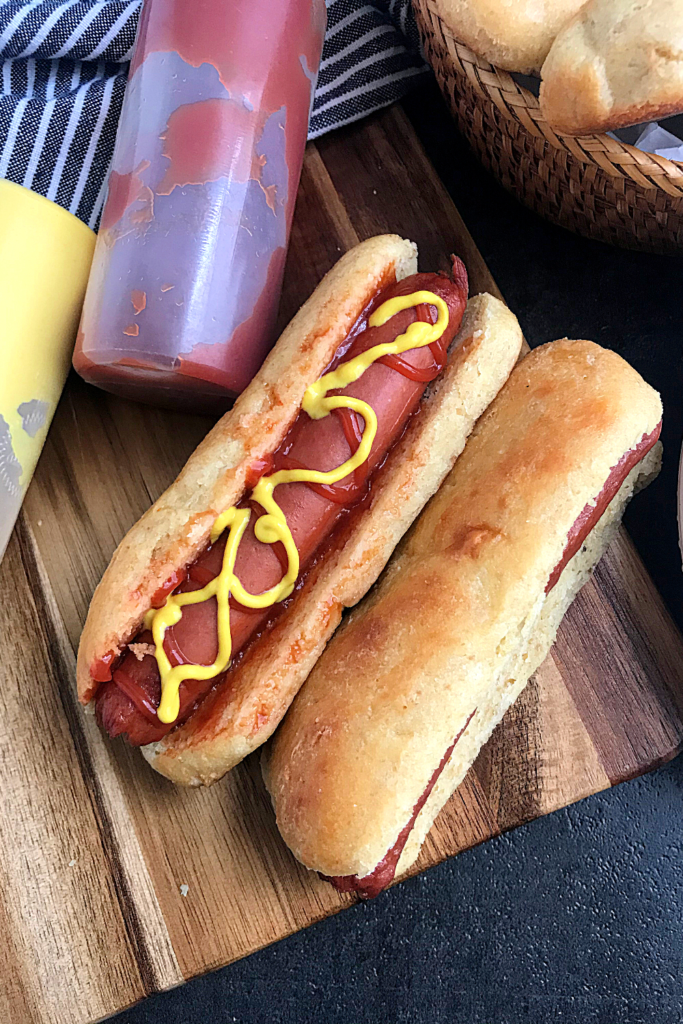 Keto hot dog bun with a basket filled with hot dog buns and 2 squeeze bottles filled with ketchup and mustard
