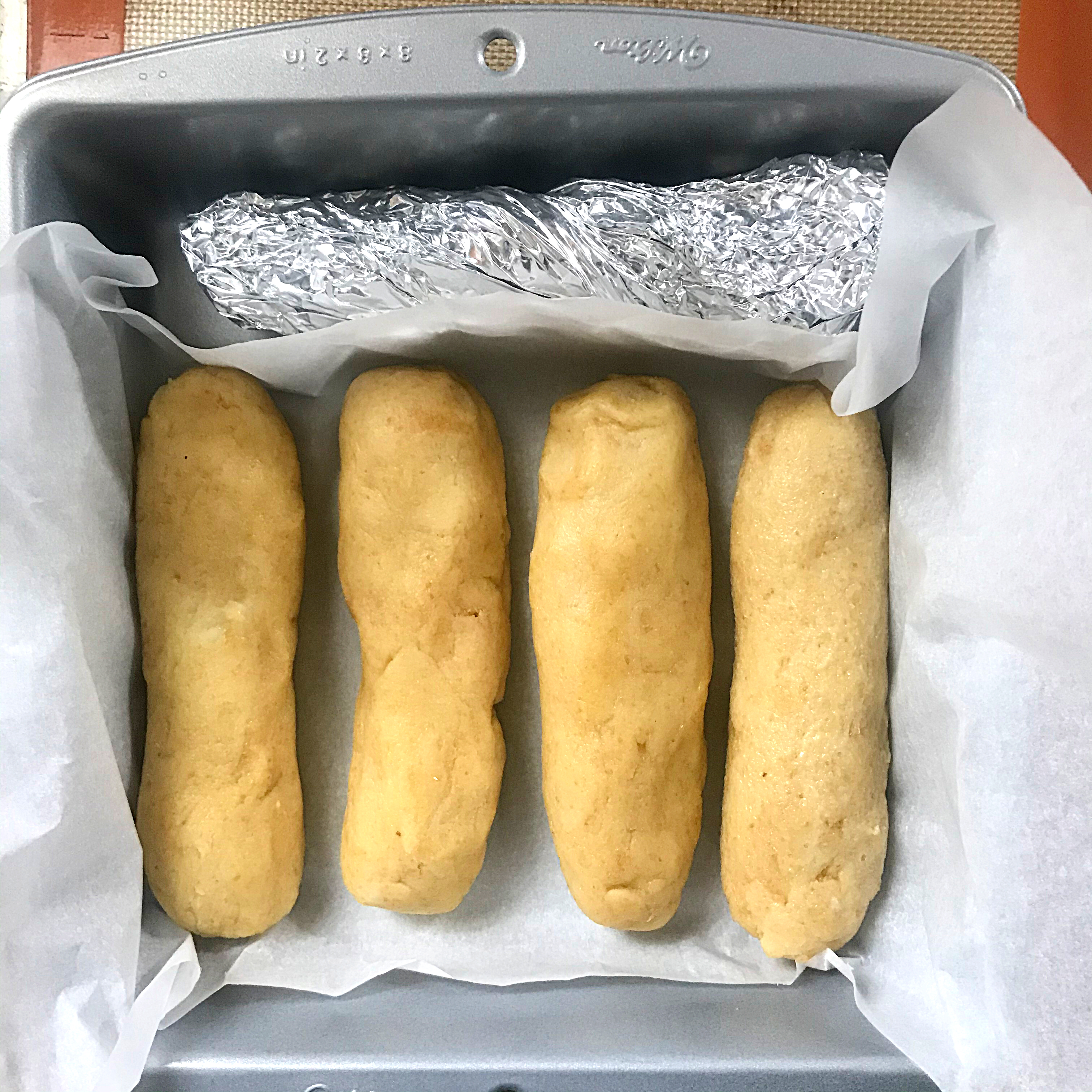 4 keto hot dog buns dough in a square cake pan