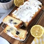 two slices cut off a lemon blueberry bread with sliced lemons at the sides.